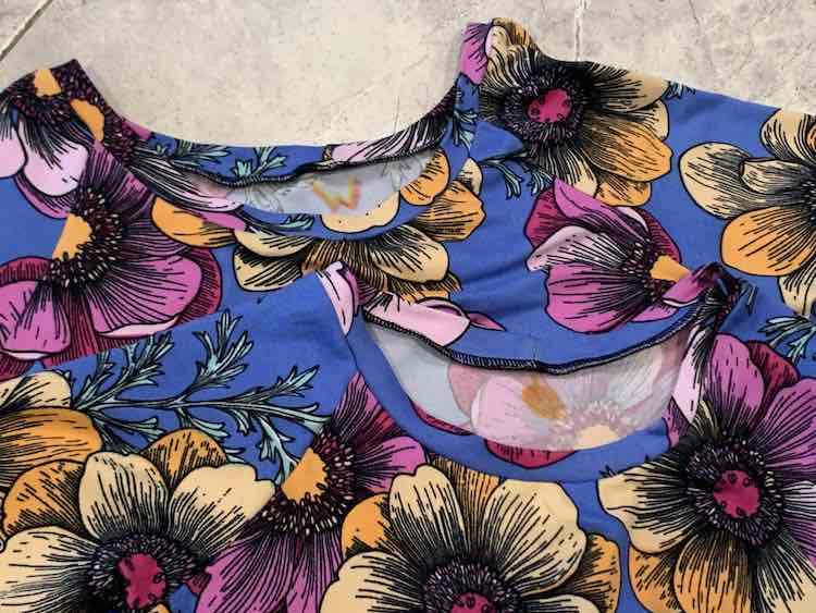 """Image shows the top of two blue shirts with pink and orange flowers laid out over top of each other on the floor. Right under the neckband, on the inside back of the shirt, sits a """"W"""" and a vague orange circle to help differentiate the two tops."""