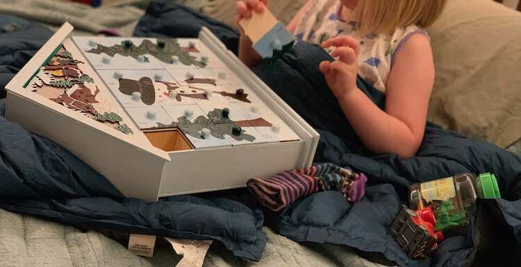 Ada sitting on the bed building hte advent calendar laid out on her lap with a sock, a car, and a container of plastic dinosaurs beside her.