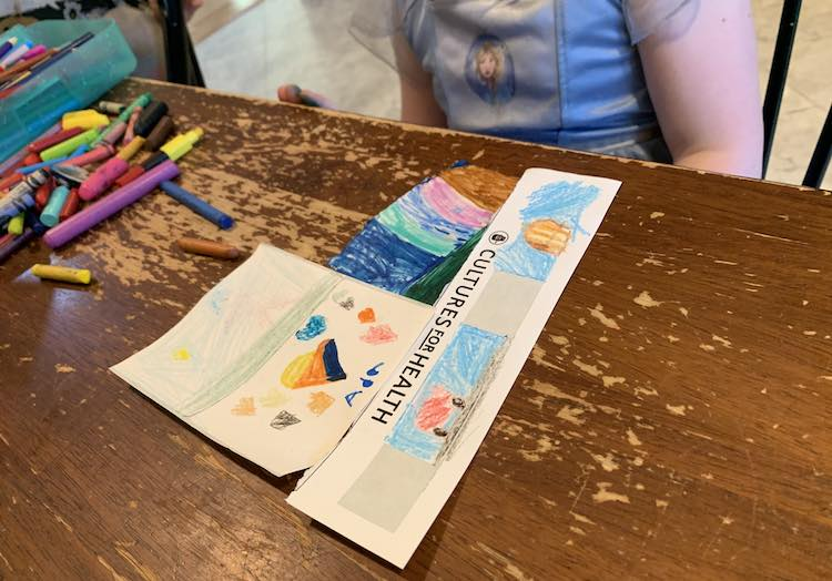 Image shows the a closeup of the kitchen table with Ada, torso shown, sitting behind it. On the table are three sheets of stickers designed with hearts, rainbows, vehicles, and a lightly colored unicorn.