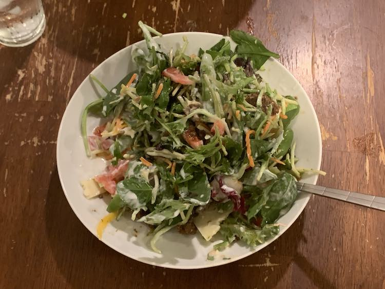 Image now shows a bowl filled with a more colorful looking salad and a fork sticking out of it with a water glass off to the upper corner. The bowl shows julienned carrots and cabbage, a salad mix, cheese, tomatoes, and yogurt 'dressing'.