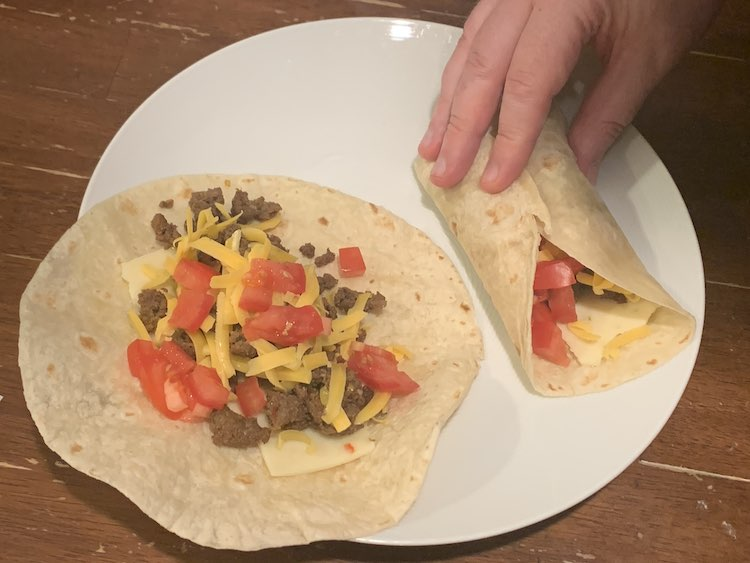 Image is focused on a white plate with an open wrap on the left and a hand holding the wrap on the right closed. Both wraps are filled with pepper jack cheese, taco meat, grated cheddar cheese, and diced tomatoes.