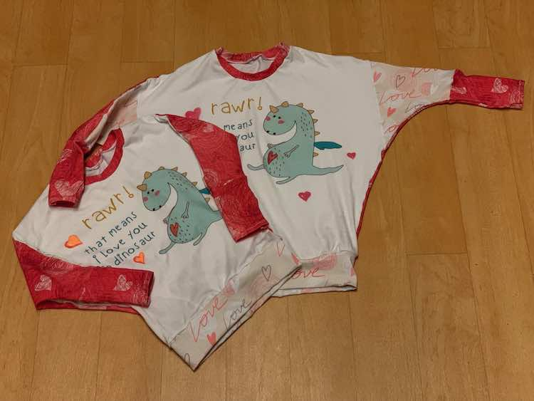 """Image shows two long sleeved shirts laid out on a floor. The bottom band at part of the front of the sleeve has pink """"Love"""" and hearts on it. The back of the sleeves, neckband, and cuffs are dark pink with hearts. The panel features a dragon, words saying """"rawr! that means I love you in dinosaur"""", and several hand drawn shaded hearts in orange (left shirt) and red (right shirt)."""