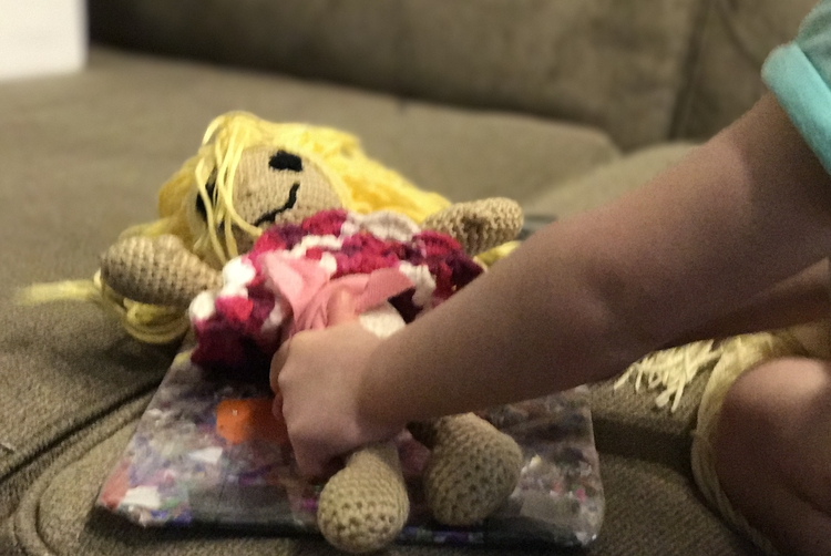 Ada reaches over and works on the diaper while the crocheted doll lays on changing pad.