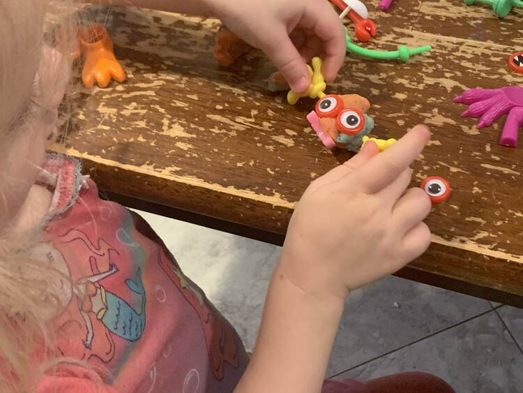 Image shows Zoey holding the hands of a little orange and blue monster with giant looking eyes, pink feet, and yellow hands.