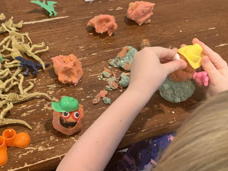 Image shows Ada adding eyes to her cowboy hat wearing playdough snowman. A little circled monster sits beside and an assortment of plastic dinosaurs and playdough pieces are scattered behind.