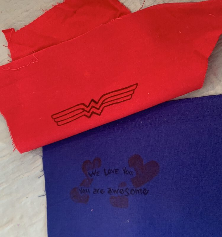 "Image shows a blue fabric with a selvedge across the top laid flat on an ironing mat. On it is written ""We love you. You are awesome"". Above it is placed red fabric with the outline of Wonder Woman's logo drawn on in back. The fabric is folded over as I try to figure out how to line it up to cover the selvedge and not the drawings."