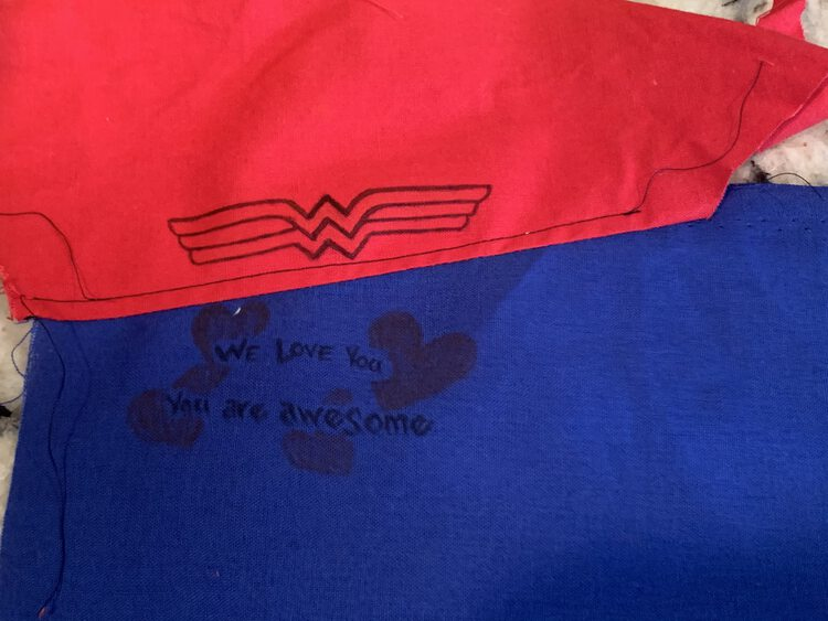 Image shows a red fabric and blue sewn together with a black line of top-stitching along the red fabric to hold the seam down. There's an outline of Wonder Woman's logo on the red fabric and a message on the blue.