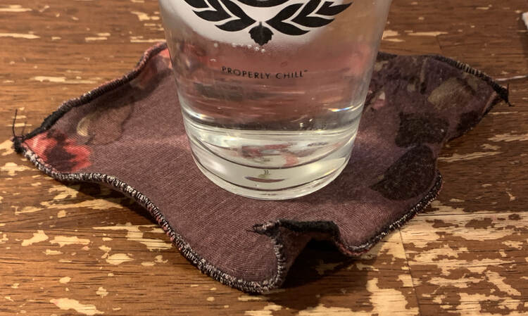 Image shows an icy glass of water sitting on a rippled black edged flowered coaster on the table.