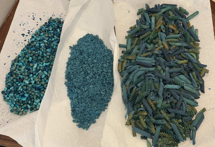 Image shows three piles of blue sensory material laid out on overlapping paper towel. From the left to right it's a mix of large pasta, rice with alphabet pasta, and two types of beans.