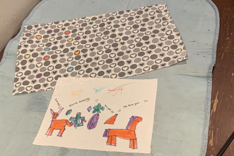 Image shows both fabrics laid out on the ironing mat at the kitchen table. The heart fabric has the odd heart colored in with yellow, red, orange, blue, or purple ink while the white fabric has unicorns, shapes, scribbles, and messages.