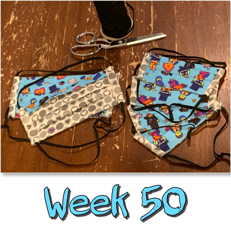 "Image shows six finished LEGO masks with black elastic behind it and a pair of scissors. Underneath it says ""Week 50"" in black outlined turquoise."