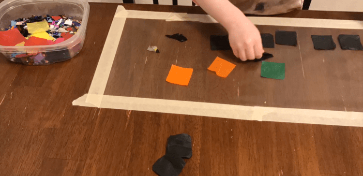Image shows the taped down clear contact paper with several black squares and some other colored squares of tissue paper on it. There's masking tape around the outer edge holding it to the table and a container of more tissue paper squares and confetti next to it.