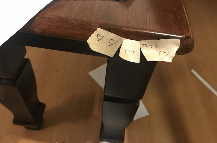 Image shows a closeup of the other end of the bench with five small pieces of masking tape still attached at the top. On them are one or two outlined hearts.