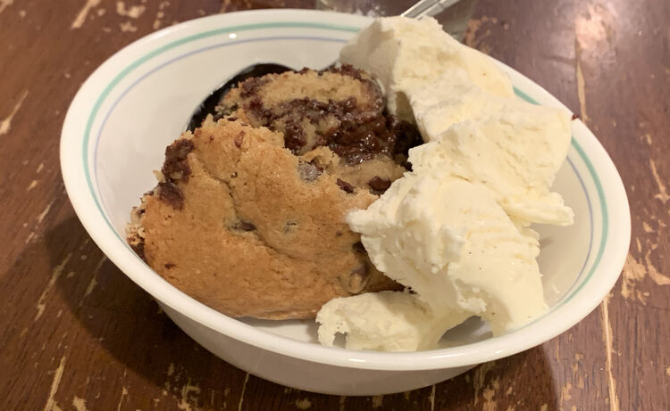 Image shows a blue lined white bowl with a slice of hot chocolate chip cookie and