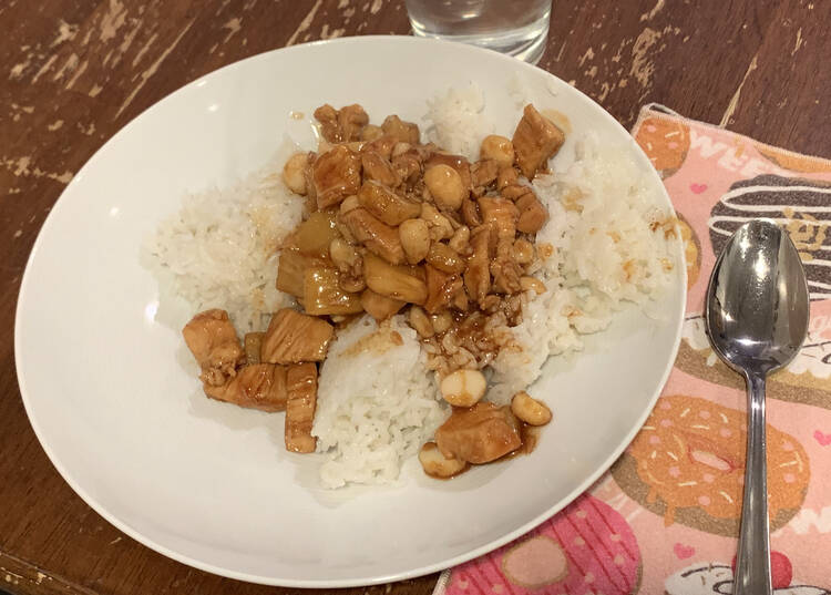 Image shows the brown colored mix served over white rice on a white plate beside a pink donut napkin and spoon.