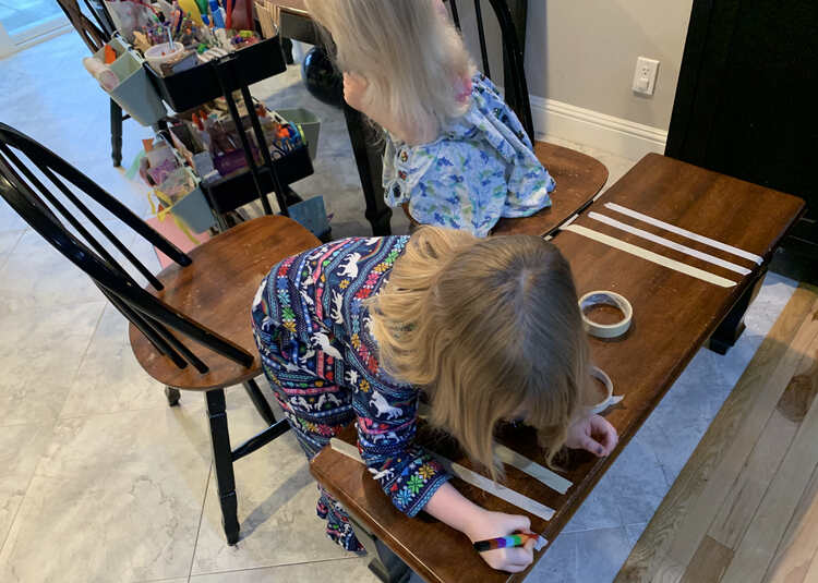 Image shows two chairs pulled up to the bench. Ada leans over her strips of tape while decorating them with a stacked crayon while Zoey is crouched in her chair and turned away from her strips as she peruses the art trolley for supplies.