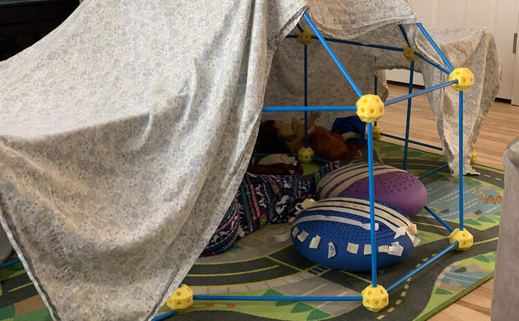 Image shows a ball and stick fort mostly covered in a top sheet. Inside are two wobble cushions covered in decorated masking tape bandages. You can see parts of one kid's nightgown as she doctors her toys.