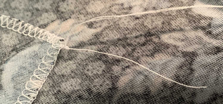 Image shows the two long thread tails going up and off the photo while the shorter one is pointed down more. At the base, against the seam and fabric, there's a small knot keeping it all together.
