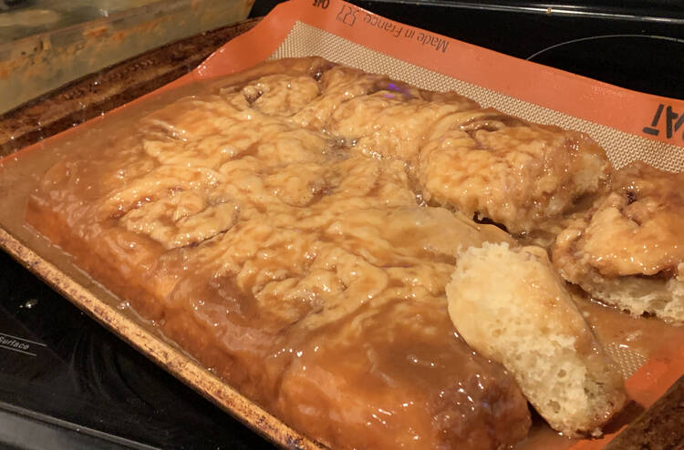 Image shows the damp and wrinkled looking cinnamon buns laid out on a Silpat lined baking sheet.
