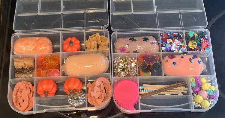 Two divided plastic containers sit out on the black stovetop. On the left sits the orange themed one while the cupcake and popsicle one is on the right.