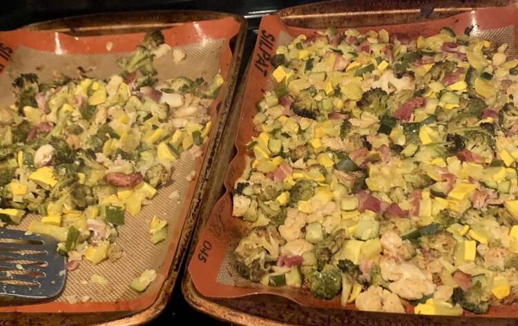 Image shows two cookie sheets side by side mostly coated in roasted bacon, cauliflower, broccoli, and squash. The left side is only half filled and a metal flipper lays across it testament to the fact that some has already been removed.