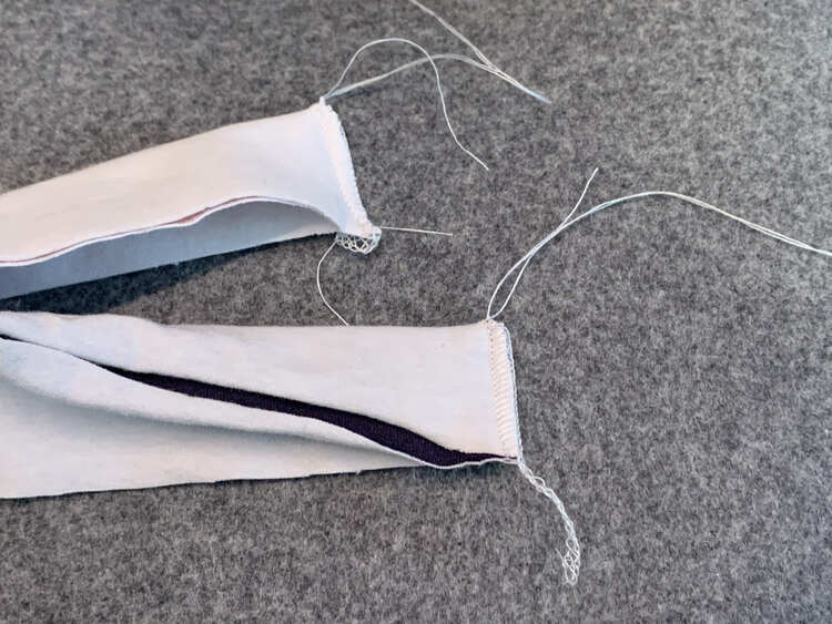 Image shows the serged ends of two different bands. Either one has a serger tail coming from the raw end while the top side, folded edge, has an unraveled tail with a knot at the base.