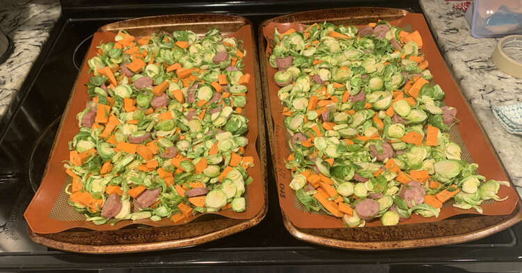 Image shows two cookie sheets laid side by side on top of the stove. They're both covered in the green, orange, and pinkish-brown food.