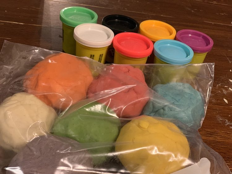 Image shows a clear freezer bag filled with seven different balls of playdough. Behind it sits the seven containers of Play-Doh filled with fresh playdough.
