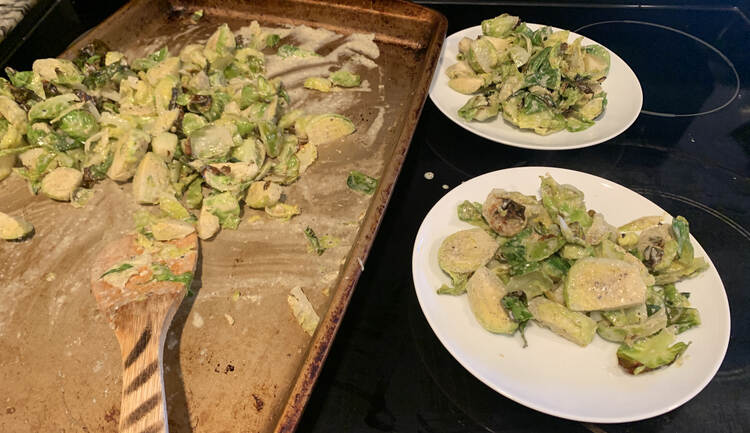Image shows a cookie sheet with a small pile of white sauce coated Brussel sprouts in a pile and a wooden spatula. Off to the right sits two other plates already dished with the Brussel sprouts.