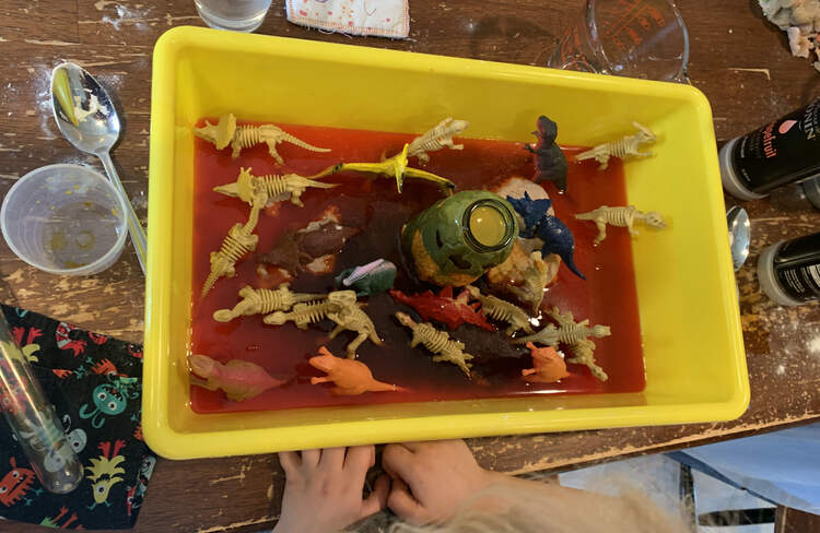 Image shows a closeup of Zoey's bin with the orange vinegar mixture rising up the dinosaurs.
