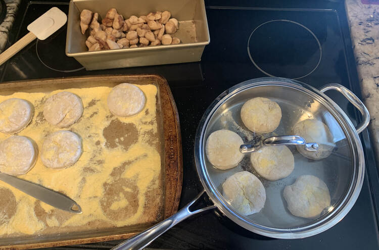 Image shows the top of the stove. To the left sits a cornmeal coated cookie sheet half filled with raw dough circles. To the right sits six English muffins frying in oil with a lid overtop. In the back sits the baked sugar and cinnamon sprinkled dough bits.
