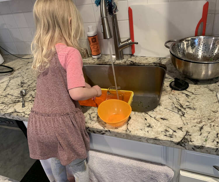 Image shows Zoey standing on chair (chair cut off) in front of the kitchen sink and towel covered cupboard doors. In the sink the yellow bin is full with orange tinted water as more water runs into it from the faucet.