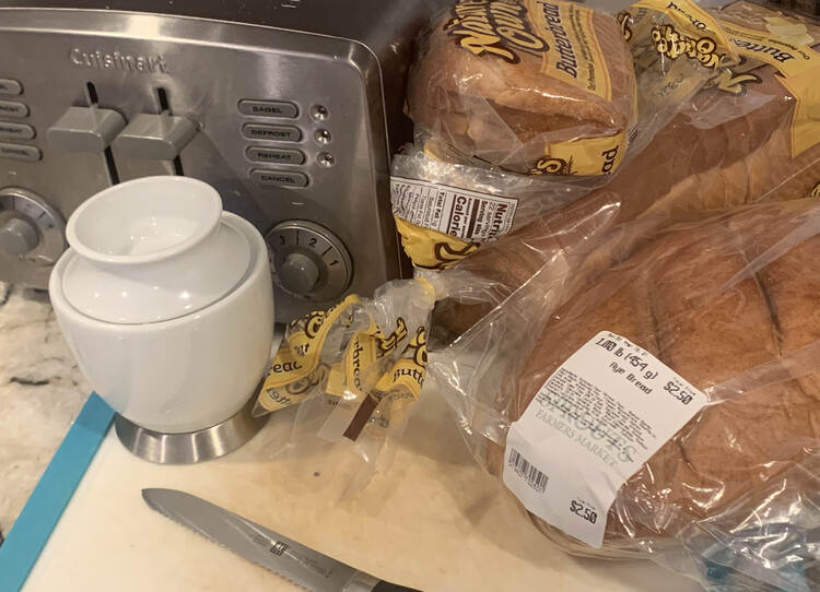 Image shows a silver toaster beside a bag of sliced butterbread. In front of it sits a while unsliced rye bread loaf, a white butter crock, a plastic cutting board, and a serrated bagel knife.