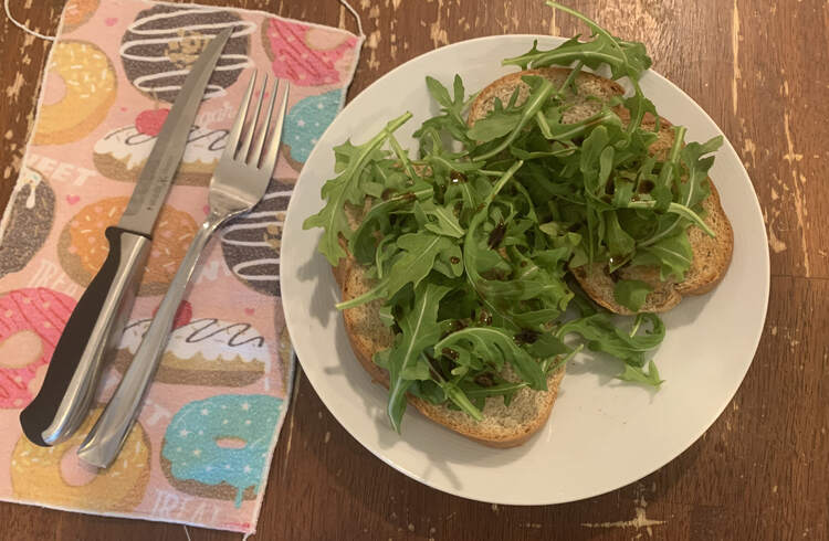 image shows two pieces of rye bread covered in leafy green arugula. You can see the odd dark splash of the balsamic vinegar that was sprinkled over top.