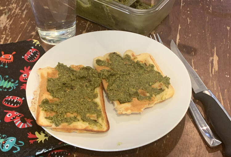 Image shows two waffles with green mixture on top on a white plate. Beside it sits a fork and knife on one side and a monster fabric napkin on the other. Behind it sits a water glass and a glass container of more pistachio pistou.
