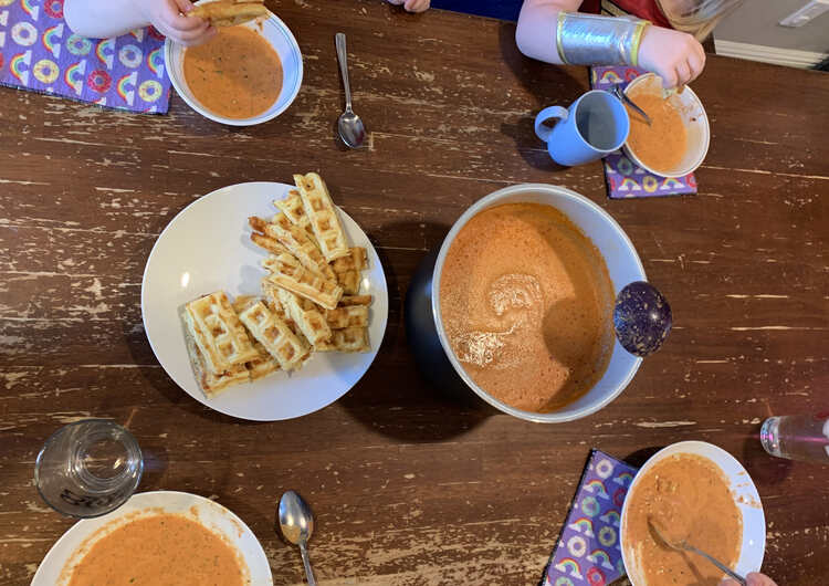 Image is taken from above showing our kitchen table with the liner of blended tomato soup next to a plate of cheesy waffle dippers. Four bowls are around it with waffles being dipped and eaten above the two smaller kid ones.