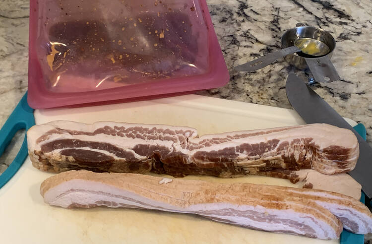 Image shows two stacks of raw bacon on a plastic cutting board. Beside it sits a sharp knife and behind it a pink Stasher bag on its side with the ingredients mixed within.