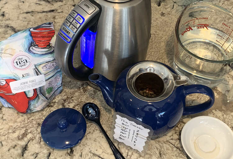 Image shows Jasmine Pearls set in the teapot with the electric kettle heating to 175° and a tea tracker set to the proper temperature and three minutes of steep time.