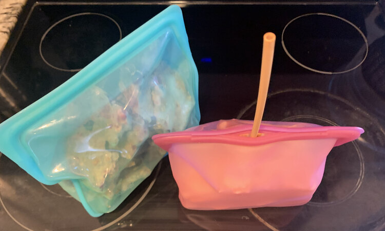 Image shows two Stasher bags side by side. The one on the left is sealed while the one on the right is mostly sealed with a straw sticking out of it.