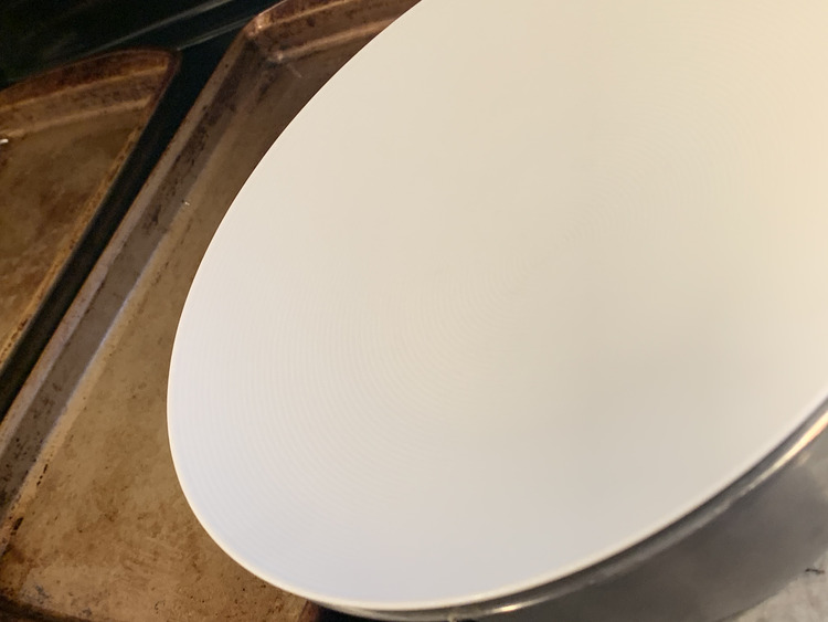 Image shows a plate laid on top of a metal bowl. Behind it you can see two cookie sheets sitting side by side on the stovetop.