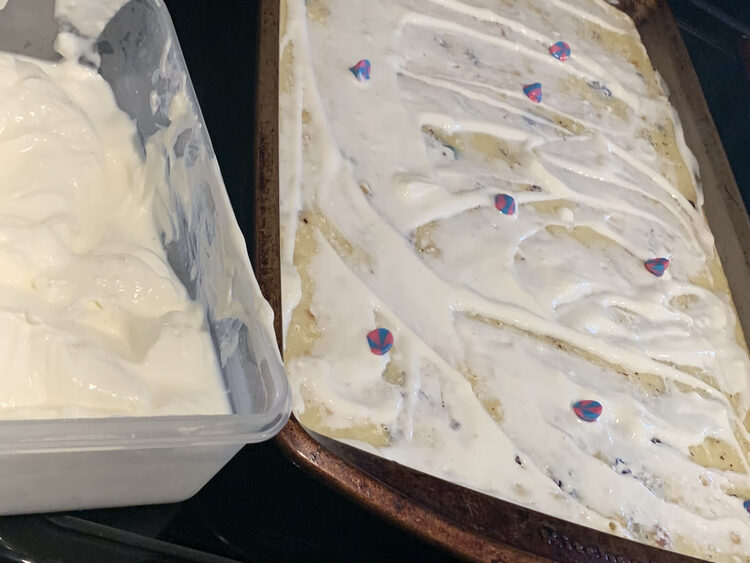 Image shows a sheet pan with white labneh spread all over it and the odd pink and blue swirled chocolate chip on top. To the left is a container of more labneh.