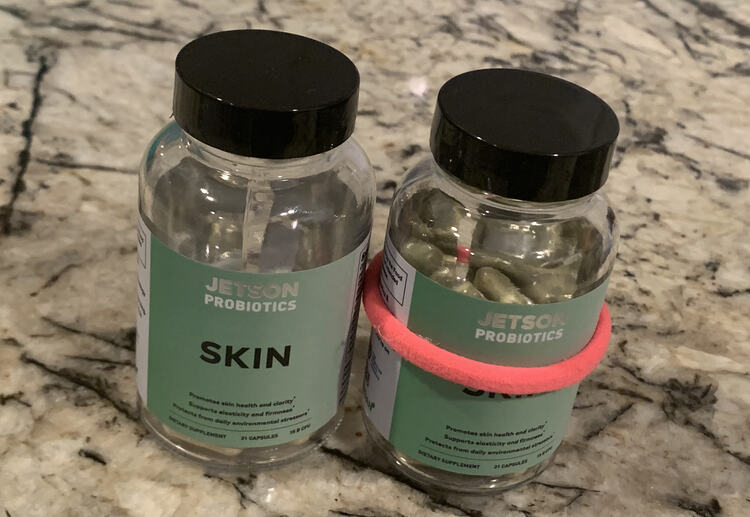 Like the before photo this one shows two bottles sitting on the counter. This time there's no napkin underneath either of them and the right one has a pink ponytail tie around it's center.