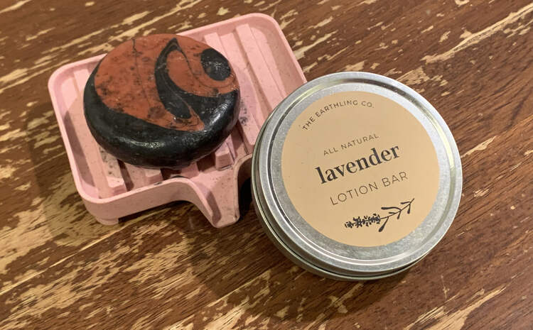 Image shows a pink plastic soap dish on the wooden table with a pink and black streaked soap on top. A closed tin containing lavender lotion is leaned against the front of the soap dish.