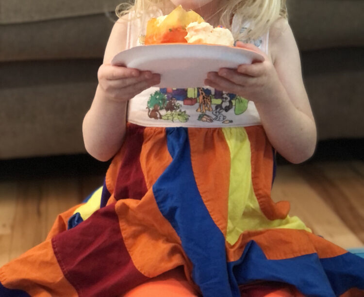 Same image as before but the paper plate is now held in front of her.