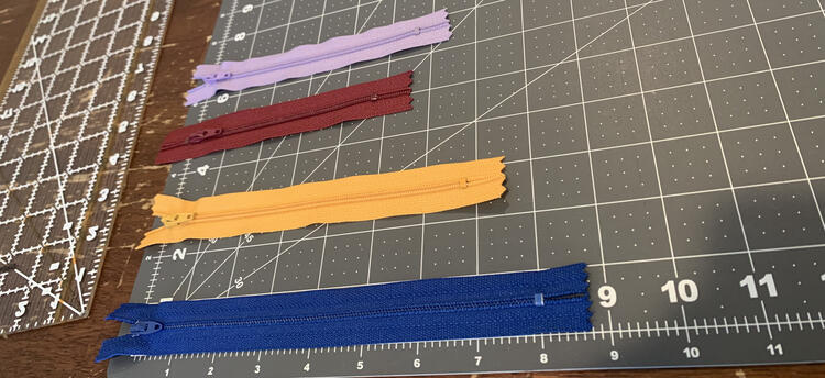 Image shows the zippers lined up on a quilting cutting board showing each of their length.