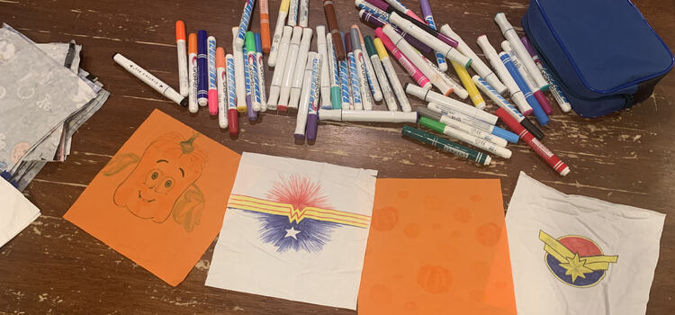 Image shows two orange squares and two white ones with fabric markers laid out on the table above them.