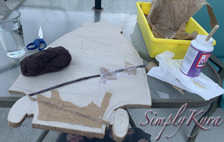 Image shows a brown ball of yarn, the skateboard with four strands glued down and brown paper for the lower half.