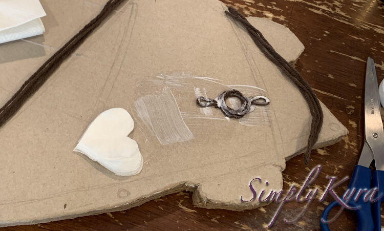 Image shows the brown circle with a loop coming from either end glued down to the cardboard skateboard and coated in more white. The section underneath has more glue showing where the heart napkin will go next.