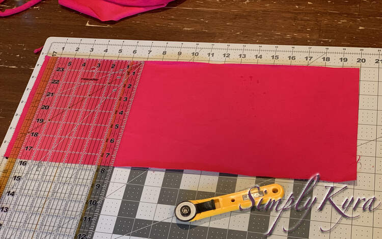 Image shows a large rectangle of pink fabric with the clear quilting ruler laid out showing it is 7.75 inches tall.