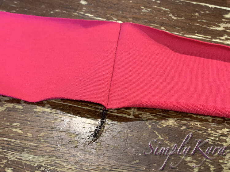 Image shows the join between the two strips with the seam on the bottom and the serger tail sticking out.
